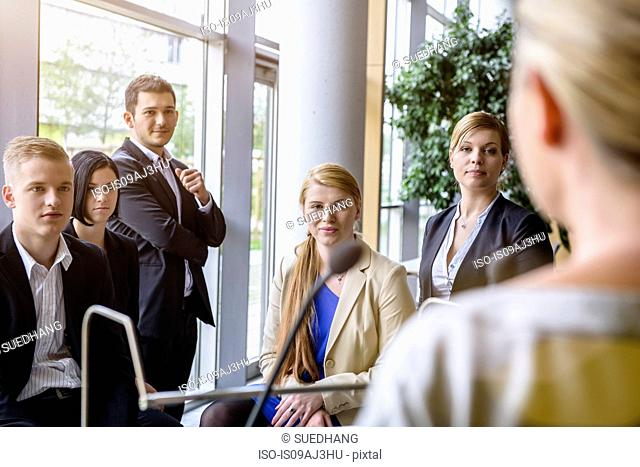 Businesswomen and men listening to speaker in office conference room