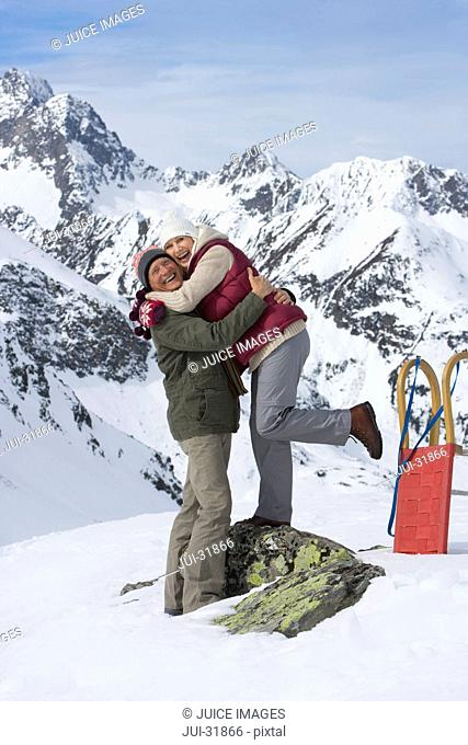 Smiling senior couple hugging on snowy mountain
