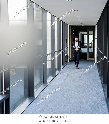 Businessman with earphones talking on smart phone in office building