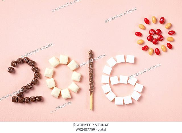 Background of new year with typographical 2016 and sun made of chocolates, marshmallows, cookie, cube sugar and jellybeans