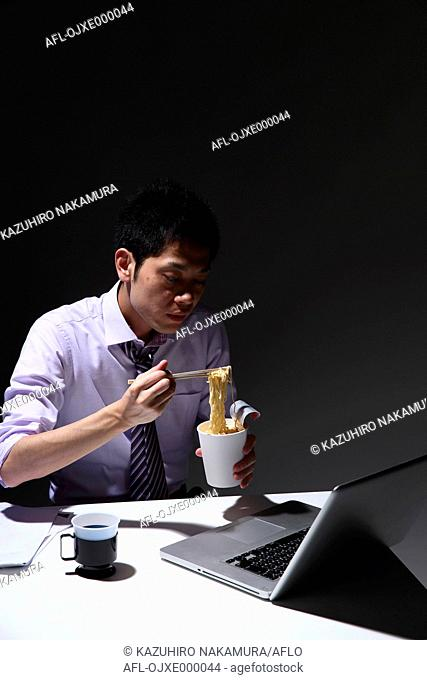 Young Japanese businessman eating at his desk