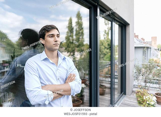 Serious man on balcony looking away