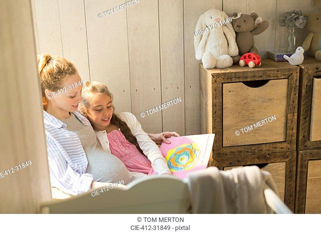 Pregnant mother and daughter reading story book in nursery