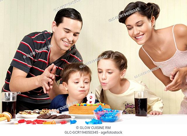 Boy and a girl blowing out birthday candles with their parents