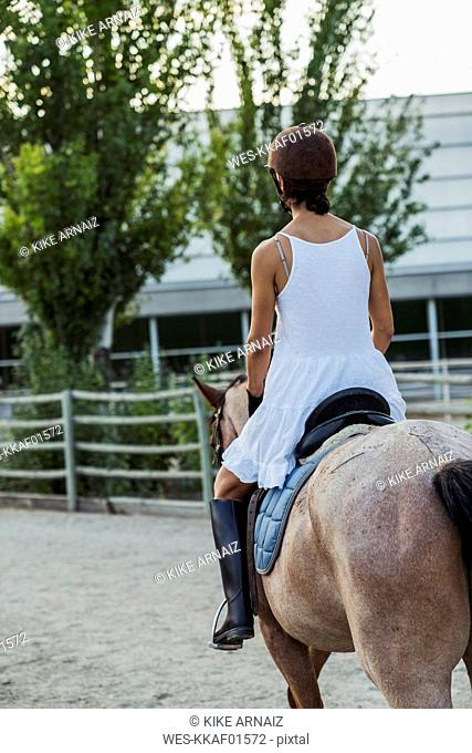 Back view of woman riding on horse