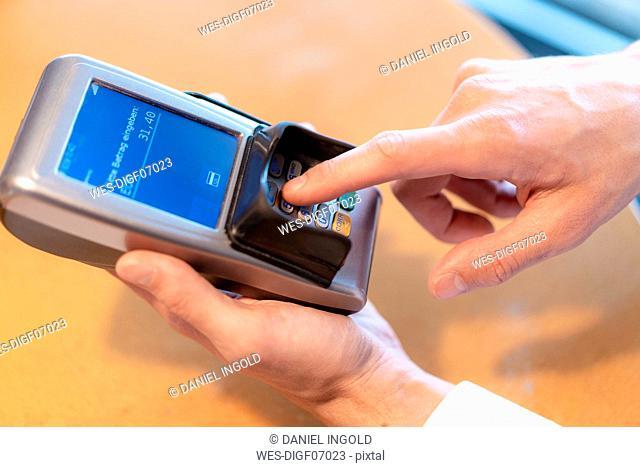 Man using credit card reader, close-up