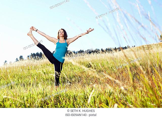 Mature woman practising yoga on field