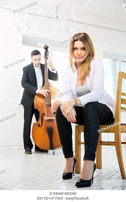 Woman on chair and man plays melody