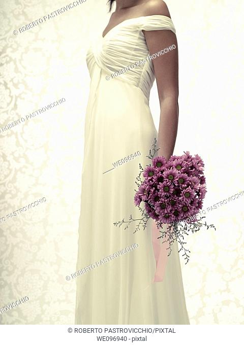 Bride in a white wedding dress holding a flower bouquet