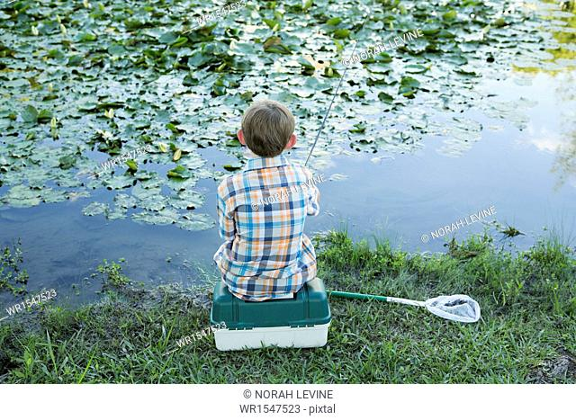 Back view of a young boy sitting on his baitbox, fishing in the river