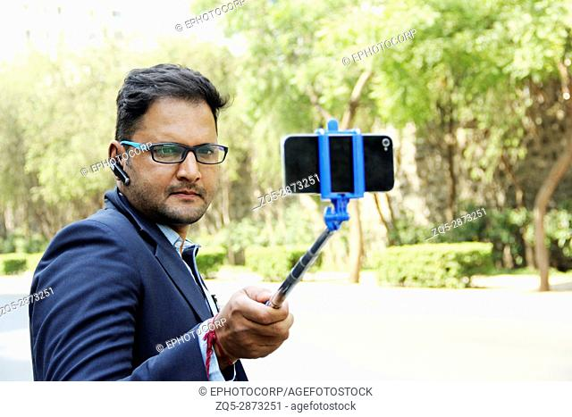 Young Indian corporate man in suit taking selfie with selfie stick