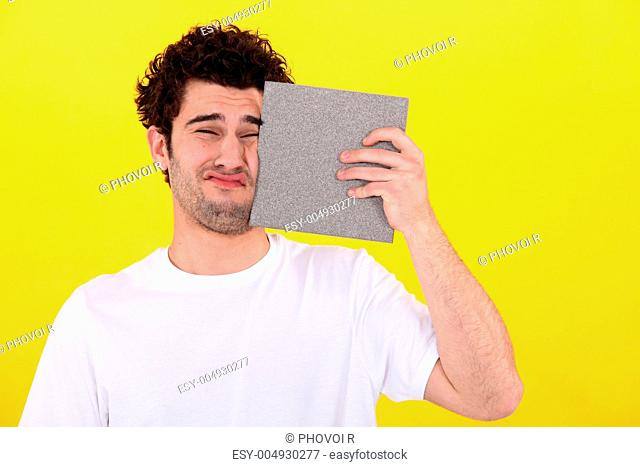 Man pressing tile against face