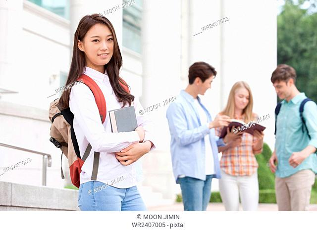 Korean female student with backpack holding a book in her arms and staring forward with a smile with the background of international students together in...