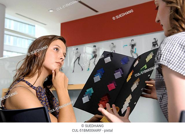 Businesswomen examining fabric swatches