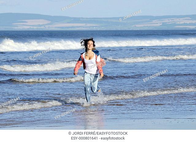 Girl running at beach, Lossiemouth, Moray, Scotland, United Kingdom, Europe