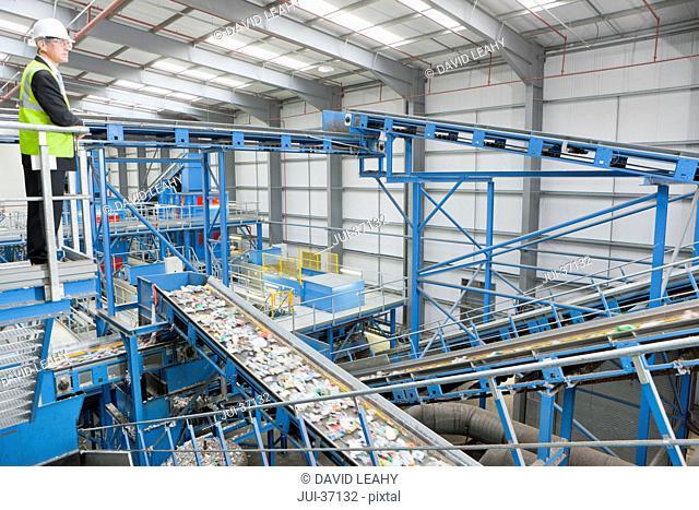 Businessman on platform above conveyor belts in recycling plant