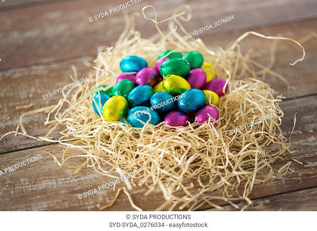 chocolate eggs in foil wrappers in straw nest
