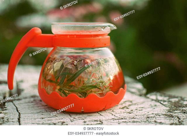teapot of fruit tea with herbs and berry on the white tree stump