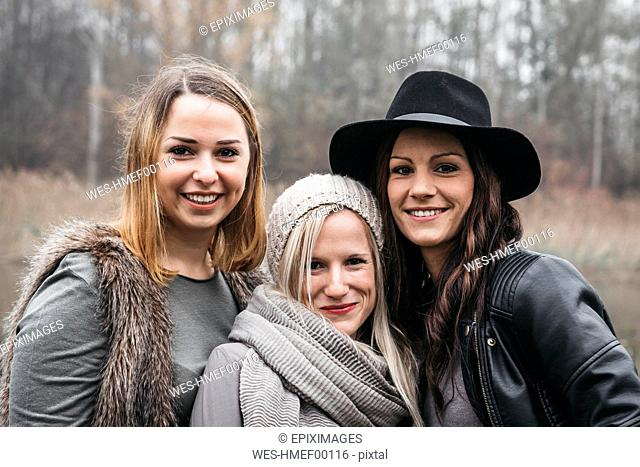 Portrait of three happy friends in autum