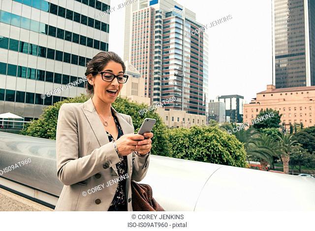 Businesswoman reading smartphone texts from footbridge, Los Angeles, USA