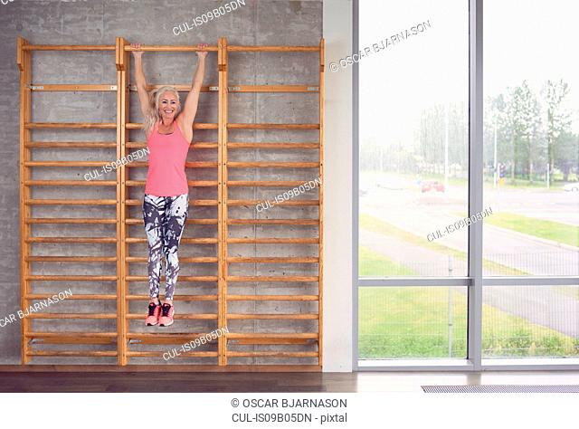 Woman stretching on wall bar in gym