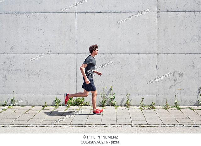 Young man running along on urban sidewalk