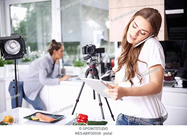 Woman using cell phone and tablet in kitchen