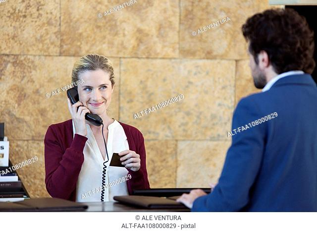 Receptionist helping customer while talking on phone