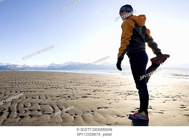 A Young Woman Stretches On The Wet Beach Before Running; Homer, Alaska, United States Of America