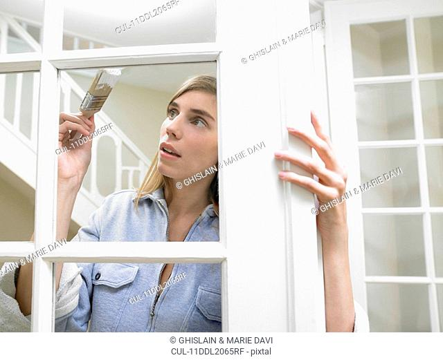 Woman painting the window frame