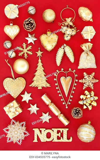 Gold noel sign and christmas tree decorations and baubles over red background