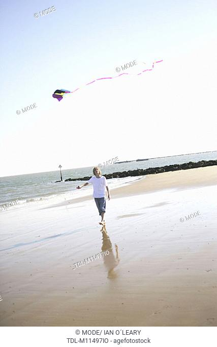 A teenager flying a kite on the beach