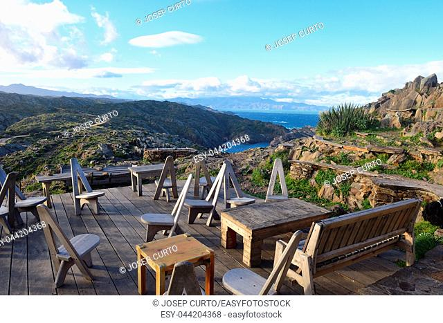 chairs on the terrace of the restaurant of Cap de Creus, Gerona province,Catalonia, Spain (background Cala Culip)