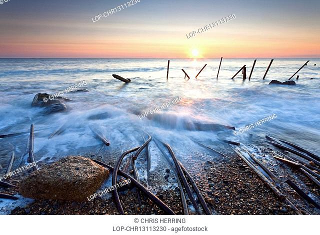 England, Norfolk, Happisburgh. Happisburgh beach and the derelict sea defences at first light on the Norfolk coast