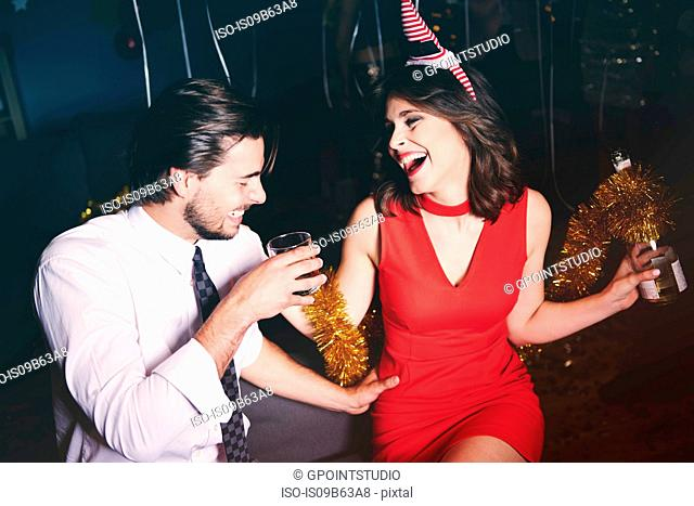 Man and woman sitting together at party, holding drinks, laughing