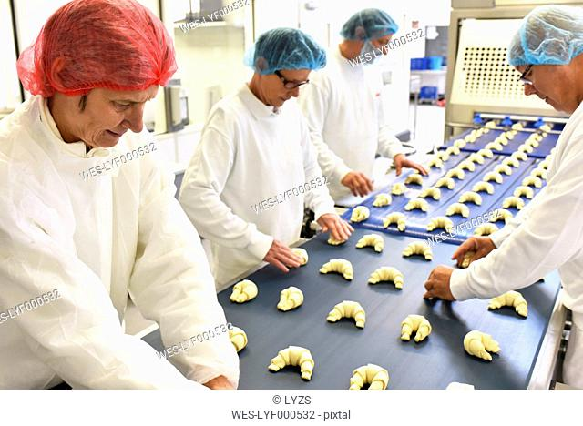 Workers at production line in a baking factory with croissants