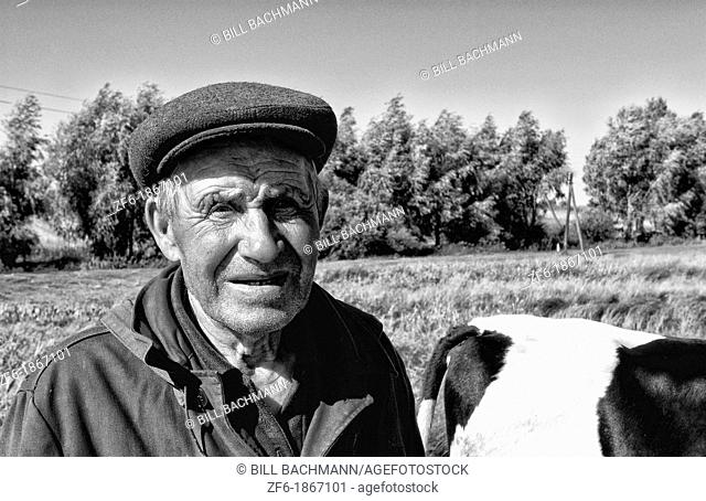 Portrait of poor farming man with his cow in rural farms between Kiev and Lviv Ukraine
