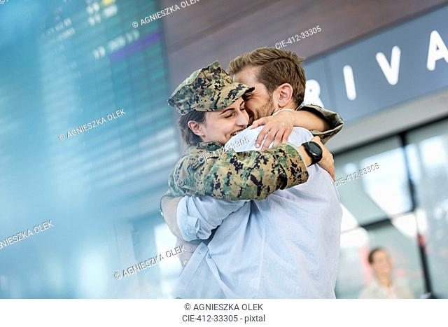 Husband greeting and hugging soldier wife at airport