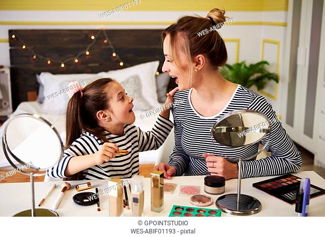 Mother and daughter applying make up together, using lipstick