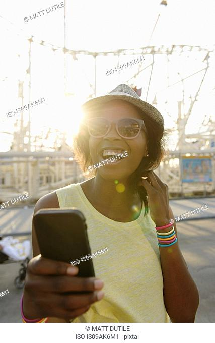 Young woman smiling for selfie on smartphone, Coney Island, Brooklyn, New York, USA