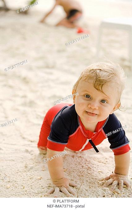 A baby crawling on a beach, the Maldives