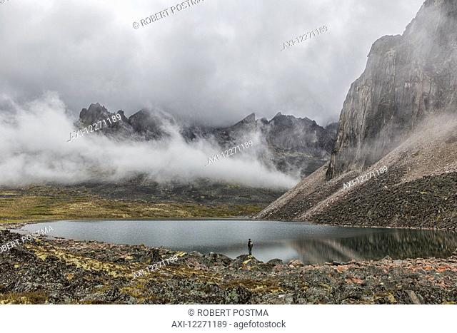 Person standing on the misty shores of Talus Lake, which lies deep within the Yukon's Tombstone Territorial Park; Yukon, Canada