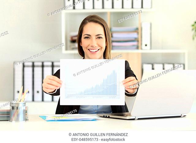 Front view portrait of a happy executive showing a growth graph at office