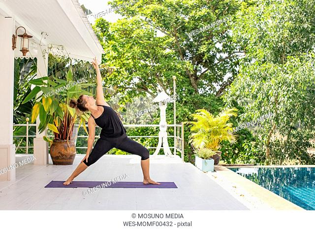 Woman practicing yoga on terrace at the poolside