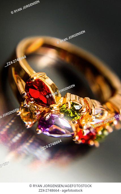 Gorgeous expensive ring still-life photo captured in a reflection off dark background. Classical solid gold jewellery