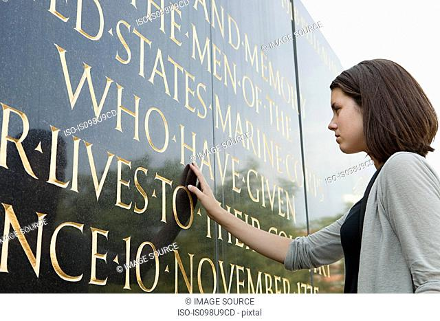 Girl looking at inscription of marine corps war memorial