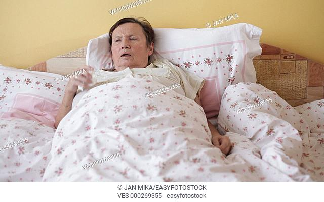Ill senior woman coughing in bed