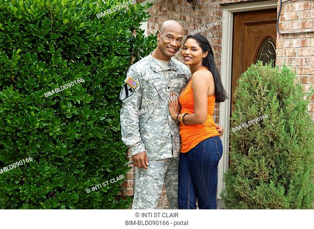 Smiling soldier and wife hugging at front door