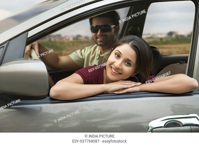 Young woman relaxing on car door during car ride