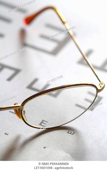 Eyeglasses next to a Snellen chart